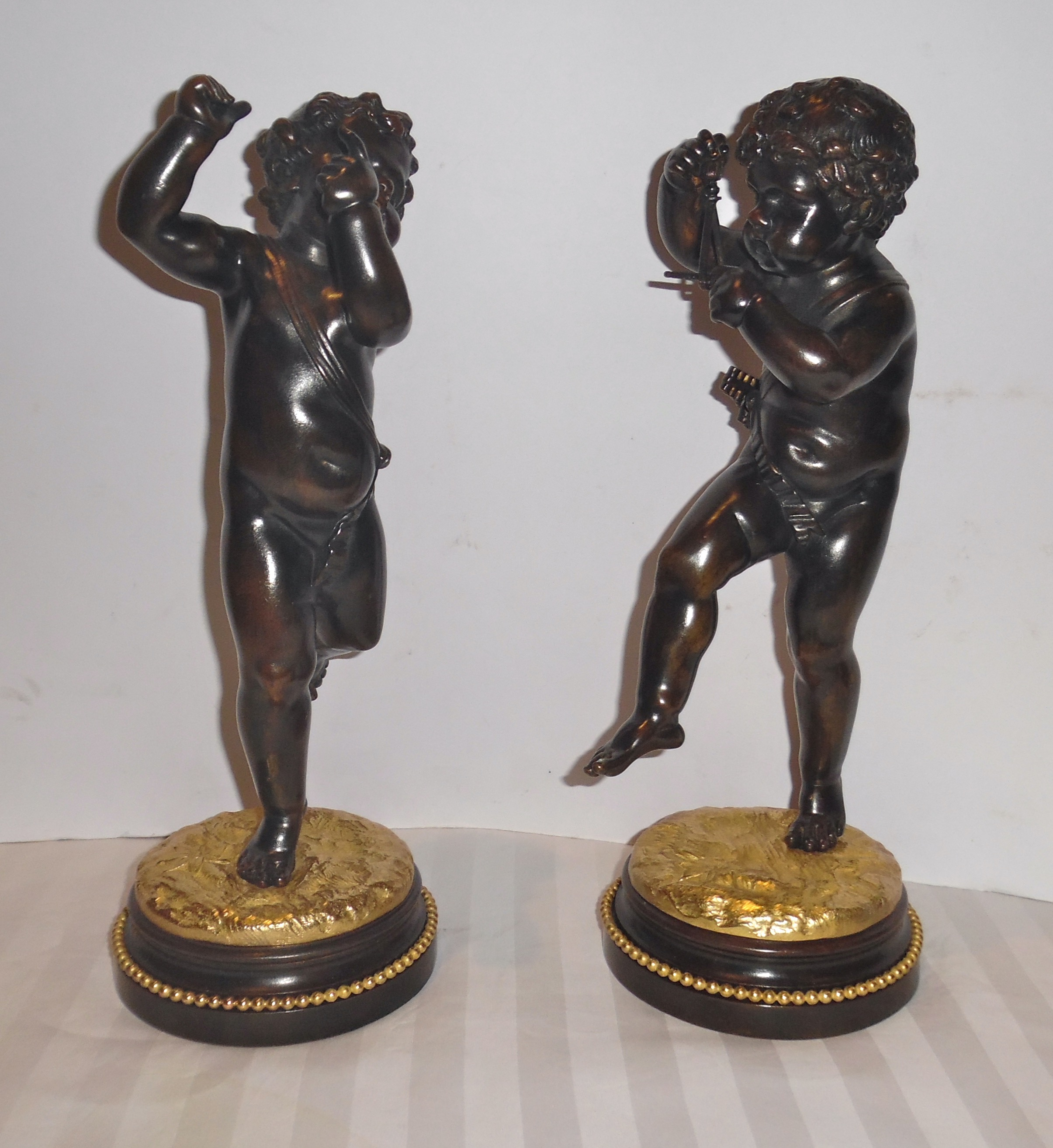 A pair of French patinated and gilt bronze cherubs